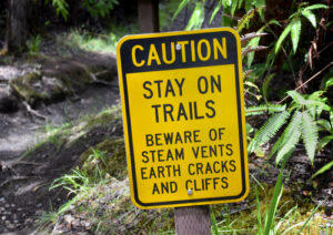 A caution sign near a hiking trail on Kilauea volcano located in Hawaii Volcanoes National Park. Hawaii travel. Things to do in Hawaii.