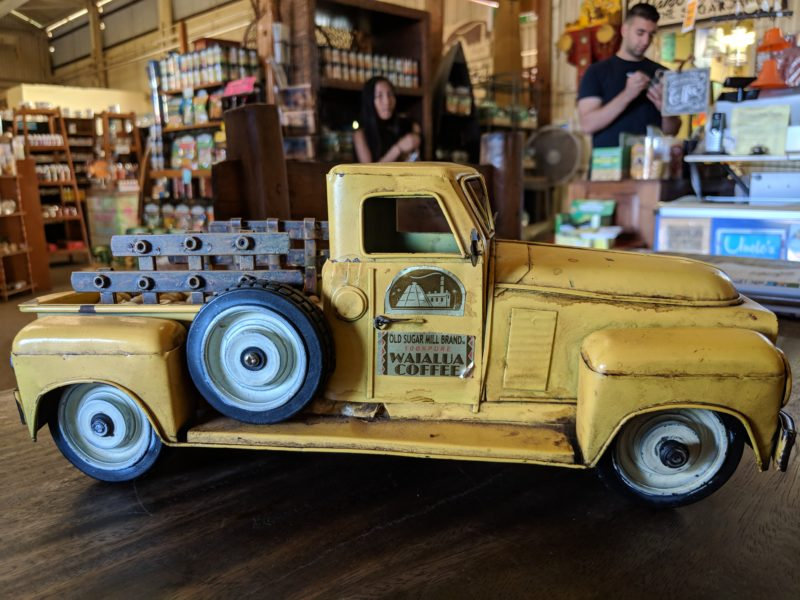 "An old school toy truck showing it's branded ""old sugar mill"" sticker can be found near the entrance of the old Waialua sugar mill."