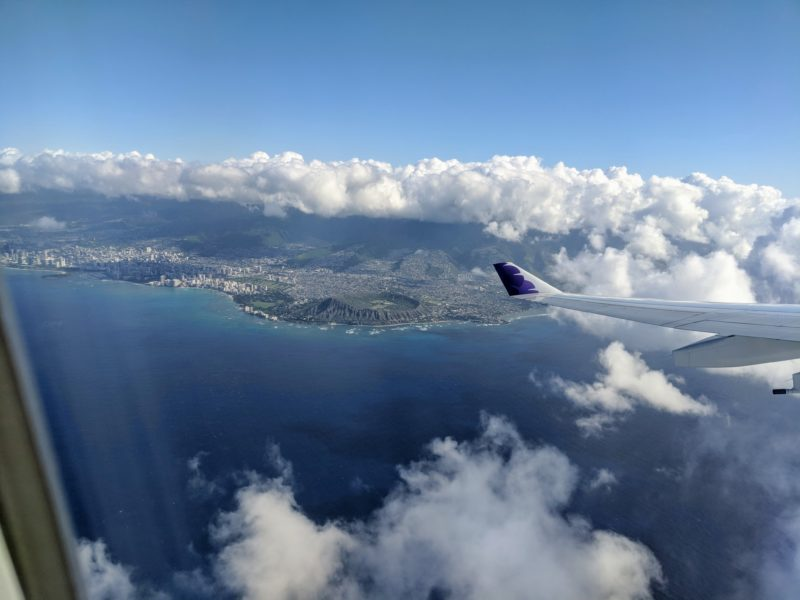 Flying away from Honolulu International Airport on a Hawaiian Airlines flight with Diamond Head peeking through the clouds.