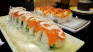 A salmon roll topped with mayo and onions at Kazoku Sushi.