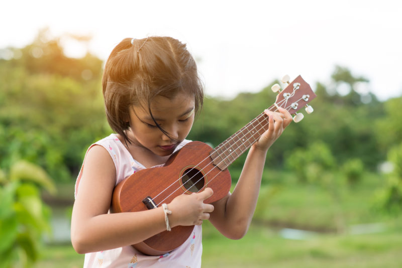 A girl playing on the ukulele from the best Hawaiian island to visit for kids.