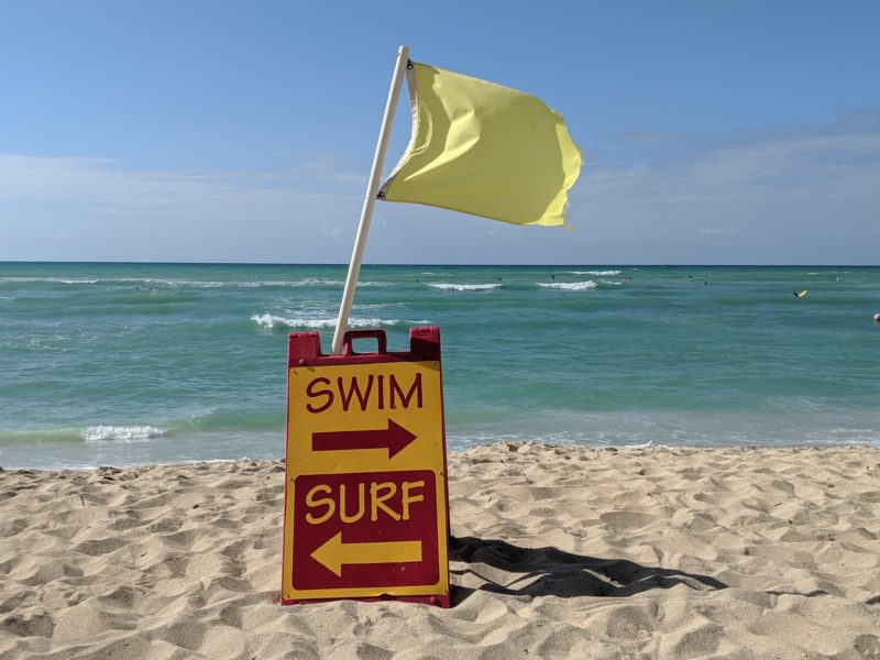 Swim and surf signs in front of the lifeguards at White Plains Beach.