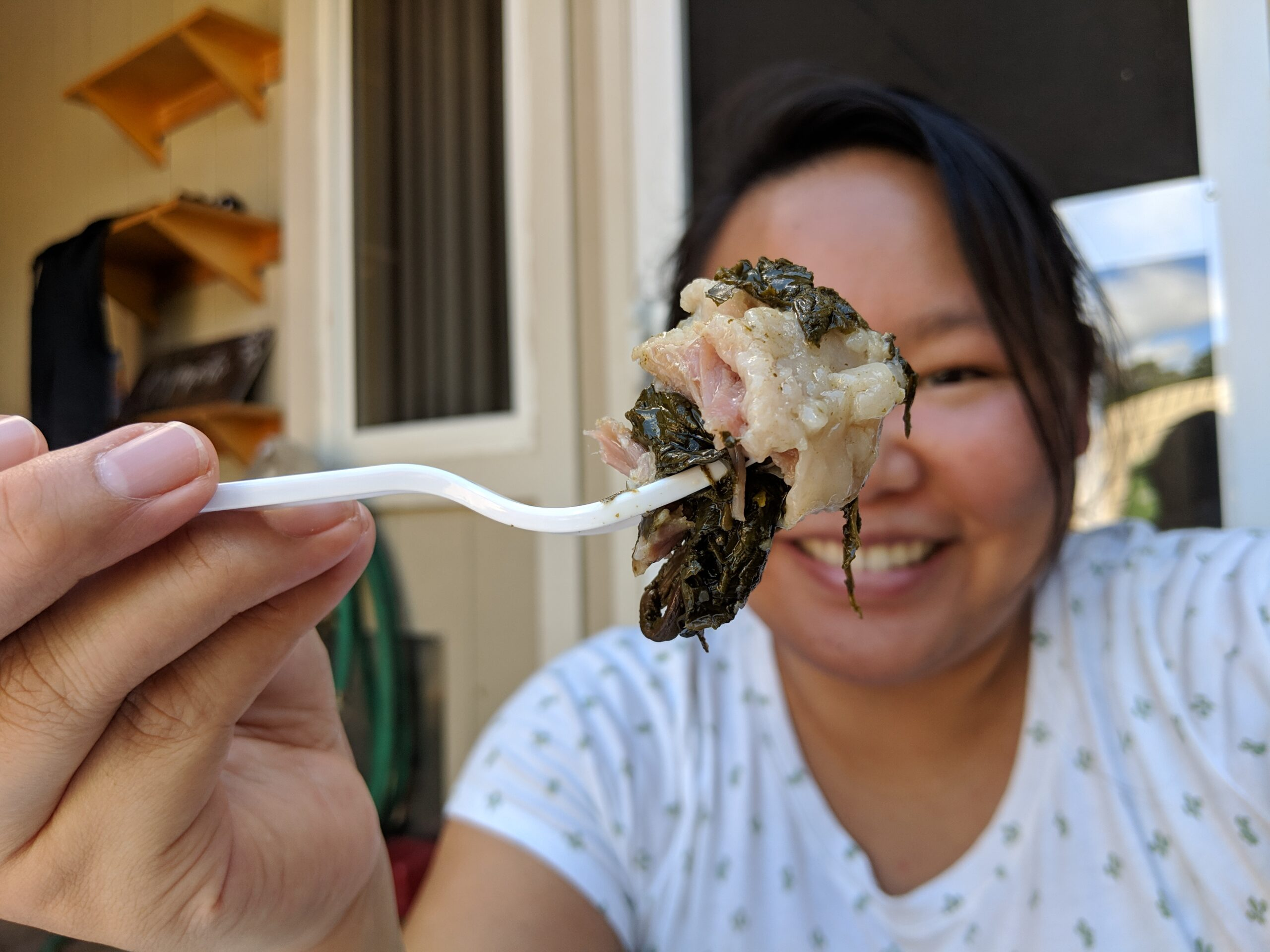 Amy eating a forkful of laulau from the side of the road.