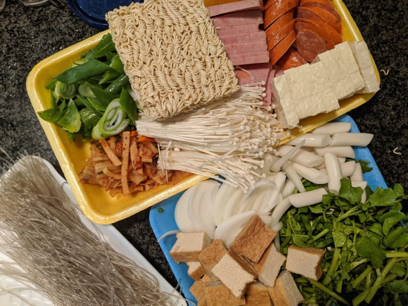Have all the budae jjigae ingredients ready as the soup heats up.