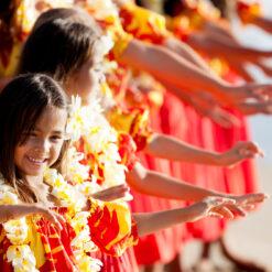 Girls dancing hula in red muumuus.