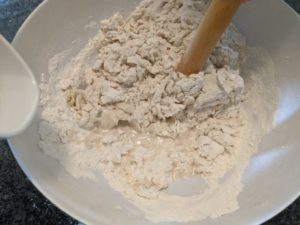 Add water a little at a time, mix, repeat, until all the loose flour is gone.