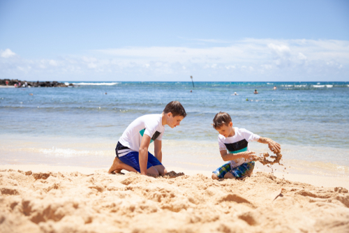 2 kids playing in the sand in Kauai.