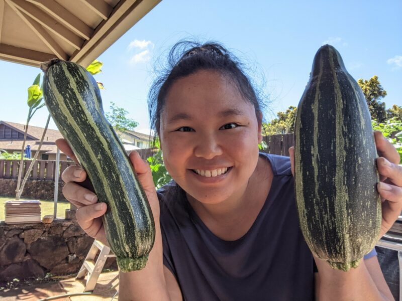 Me holding 2 cocozelle zucchinis. Living in Hawaii & things to do in Hawaii.