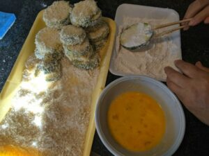 Dipping the zucchini slices in flour, egg, and panko.