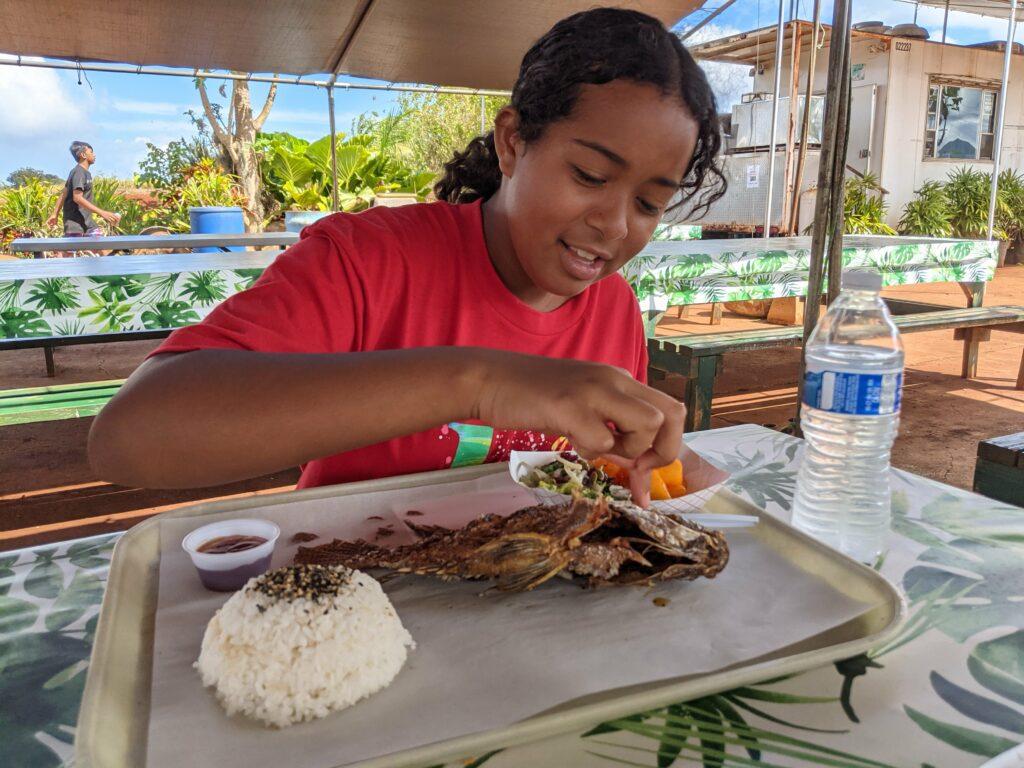 One of the girls enjoying her freshly caught tilapia.
