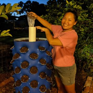 Amy with her DIY vertical garden with compost tube.
